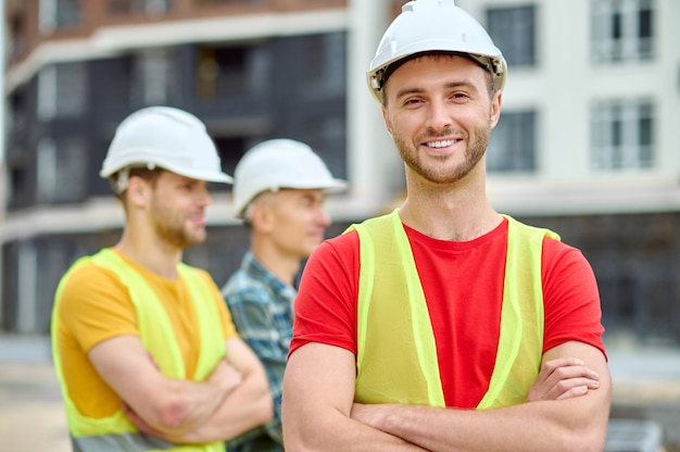 High-spirited construction worker in a protective helmet looking ahead