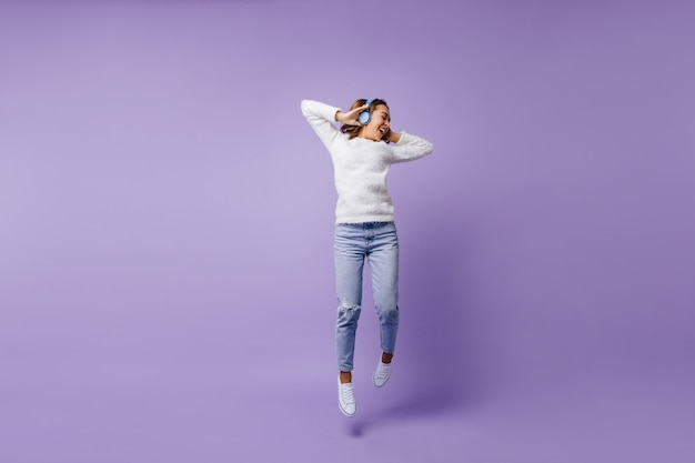 High-spirited lucky female student jumping. full-length portrait of girl in fashion white sweater and light blue jeans.