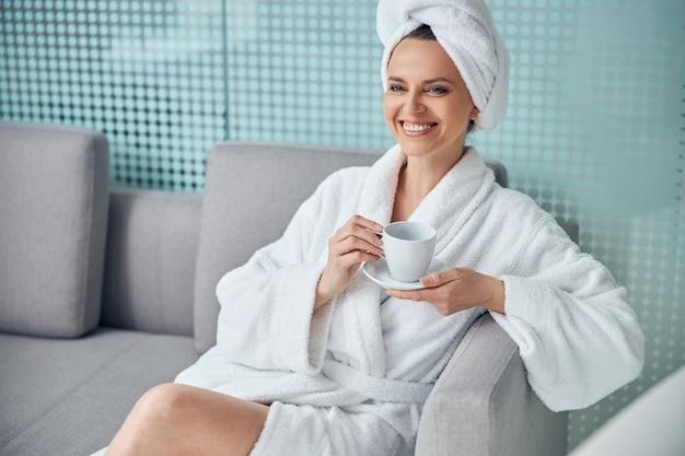 커피 한 잔과 접시가 소파에 앉아있는 고열 젊은 여성
