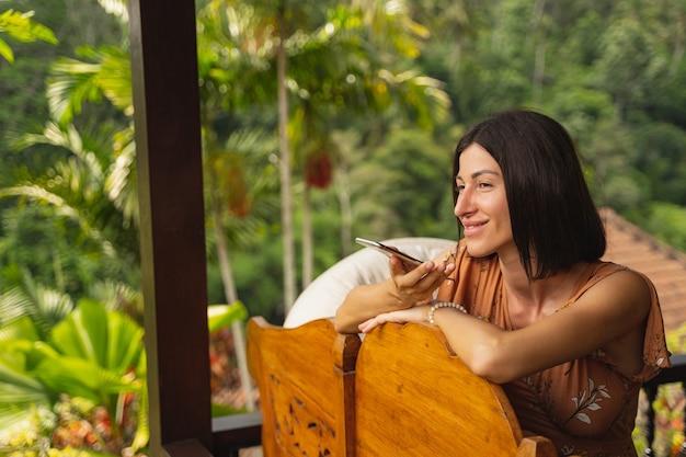 좋은 원기. 열대 풍경을 즐기고 방갈로에서 전화로 이야기하는 매력적인 젊은 여성