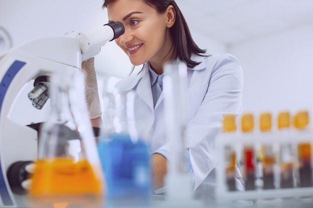In high spirits. content professional biologist wearing a uniform and looking into the microscope