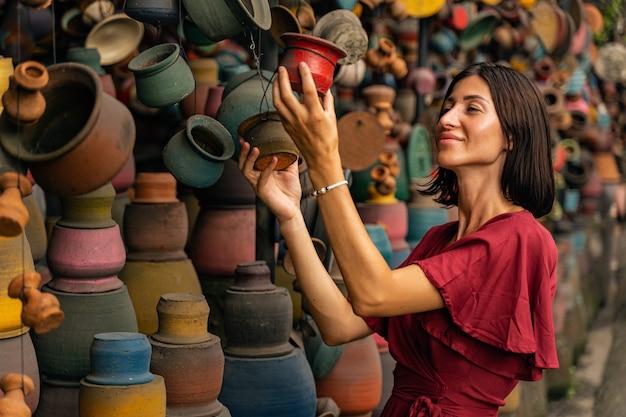 좋은 원기. 반 위치에 서서 다채로운 도자기를 보고 있는 기뻐하는 젊은 여성