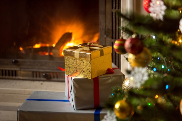 燃える暖炉のあるクリスマスプレゼントの高いスタック