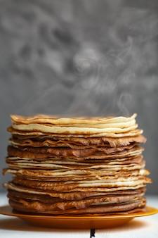 古典的なロシアの薄いパンケーキの高いスタック。素朴なスタイル。ロシアのパンケーキウィークmaslenitsaの伝統。