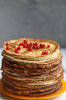 赤すぐりのベリーと古典的なロシアの薄いパンケーキの高いスタック。素朴なスタイル。ロシアのパンケーキウィークの伝統(マースレニツァ)