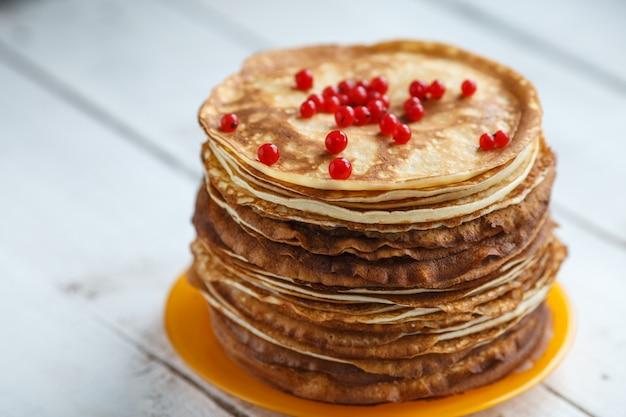 赤スグリと古典的なロシアの薄いパンケーキの高いスタック。素朴なスタイル。ロシアのパンケーキウィークmaslenitsaの伝統。
