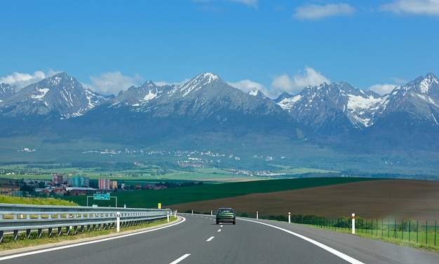 High tatras spring view with snow on mountainside and highway (slovakia)