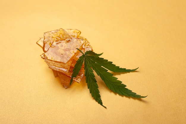 High thc, pieces of yellow cannabis wax and green leaf, marijuana concentrate.