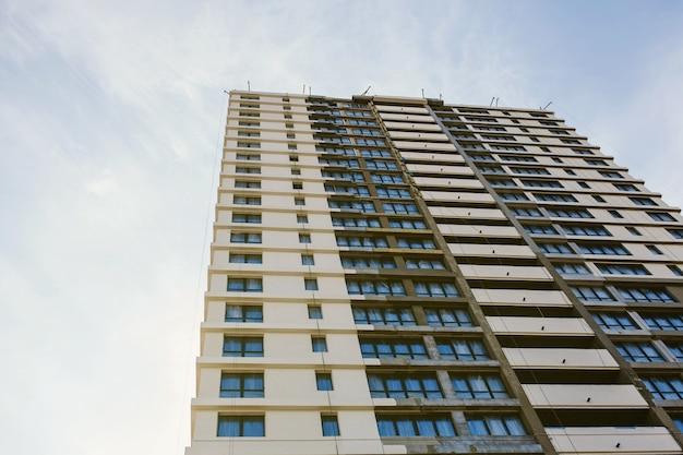 窓のある未完成の高いモダンな建物。建設と住宅ローン