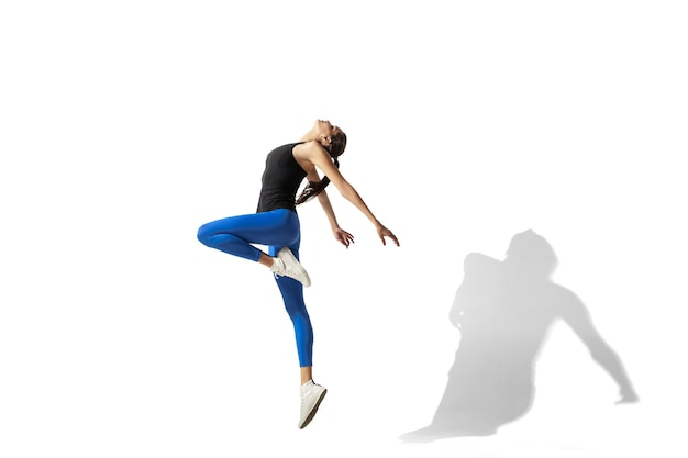 High up. beautiful young female athlete stretching, training on white studio background, portrait with shadows. sportive fit model in motion and action. flexibility, healthy lifestyle, style concept.