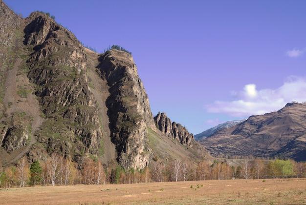 Высокие отвесные скалы над горной долиной белые облака в чистом голубом небе природа сибири