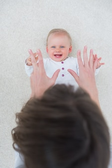 High view of a baby lying on back while playing