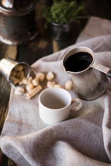 Высокий вид ткани мешковины с чашкой кофе и сахаром