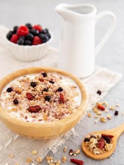 Cereali di alta vista in ciotola di legno e latte