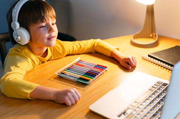 Bambino di alta vista che segue corsi virtuali