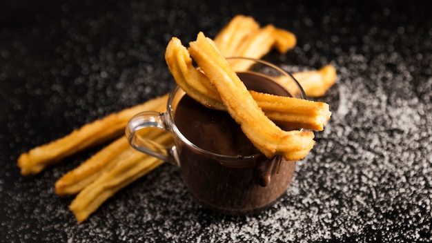 High view churros and cup of melted chocolate