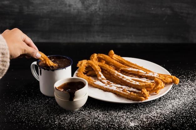 Высокий вид чуррос на тарелке с кружками сладкого шоколада Бесплатные Фотографии