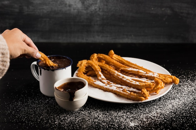 High view churros on a plate with mugs of sweet chocolate