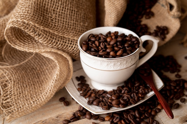 High view cup of coffee beans and burlap sack