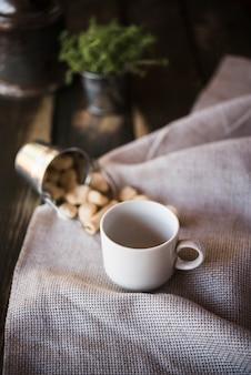 Высокий вид чашка кофе и сахар на ткани мешковины