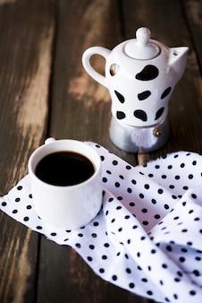 Высокий вид симпатичной пунктирной ткани и чайник с кофе