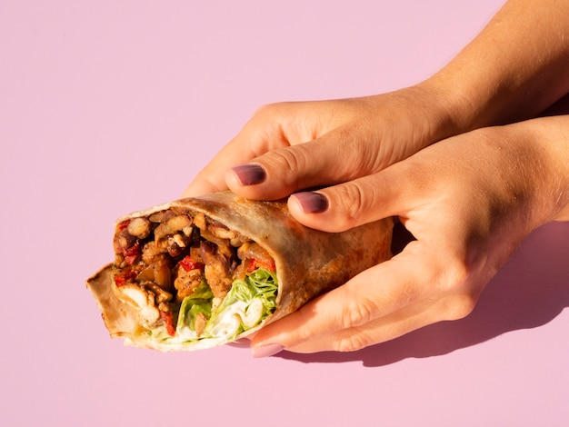 High view delicious mexican taco held in hands