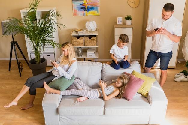 Высокий вид семьи тратят свое время на мобильном телефоне