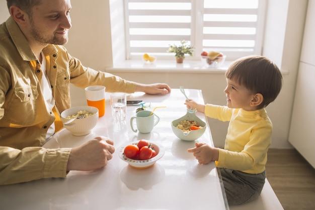 Высокий вид семьи, принимая завтрак на кухне