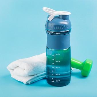 Bottiglia d'acqua fitness ad alta vista con asciugamano e pesi