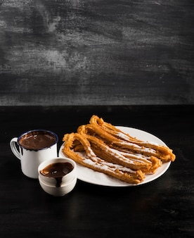 High view fried churros on a plate with mugs of chocolate