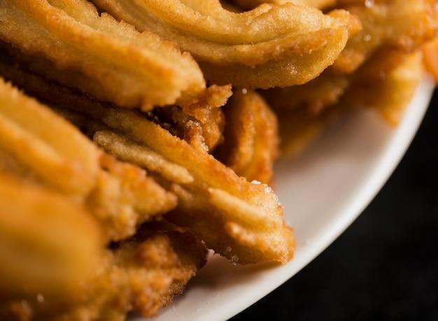 Churros fritti alta vista su un piatto bianco