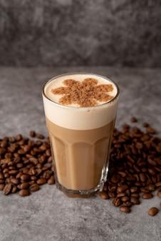 Высокий вид стакан капучино с кофе в зернах