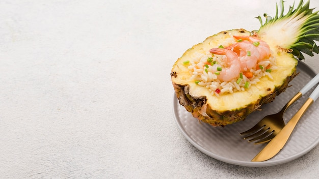 High view half of pineapple with seafood and copy space