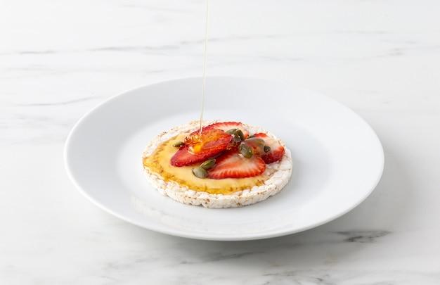 Pasto ad alta vista con torta di riso e metà delle fragole