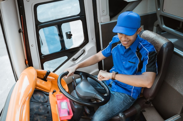 버스에서 운전대를 잡고 그의 시계를보고 제복을 입은 남성 운전자의 높은보기
