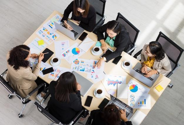 さまざまなチャートやグラフの紙が置かれた木製の会議用テーブルの高いビューと、6人のビジネスウーマンがテーブルの周りでタブレットやラップトップに取り組んでいます。ビジネス会議のコンセプト。