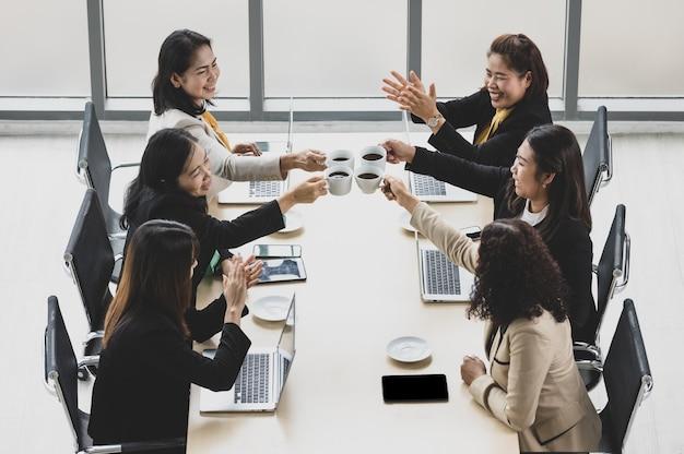 木製の会議テーブルの周りに一緒に座って、オフィスのテーブルにラップトップやタブレットと一緒にコーヒーマグを応援し、チャリンという音を立てる6人のビジネスウーマンの高いビュー。ビジネス会議のコンセプト。