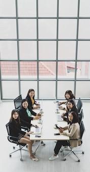 オフィスの会議室の木製の会議テーブルでラップトップとタブレットを使用して各椅子に座っている6人のエグゼクティブビジネスウーマンのハイビュー。ビジネス会議のコンセプト。