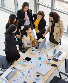High view of one business woman working on laptop and five business woman surrounding her looking at laptop in meeting room. concept for business meeting.