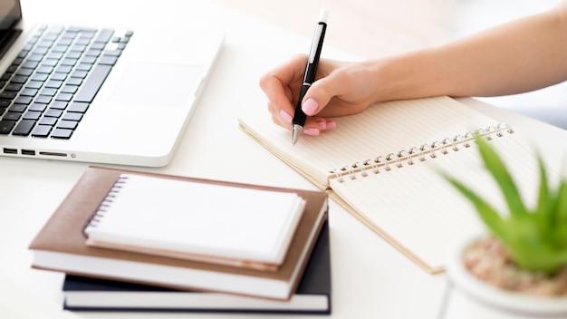 Высокий вид человека, пишущего в блокноте