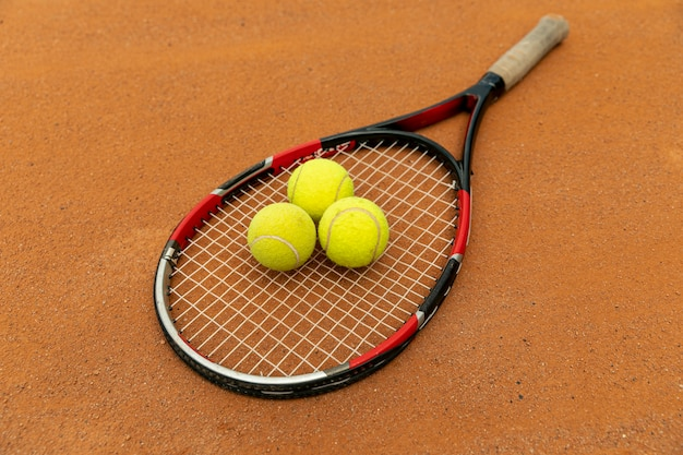 High view racket and tennis balls on court ground