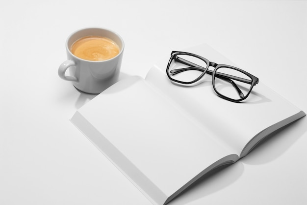 High view reading glasses and cup of coffee