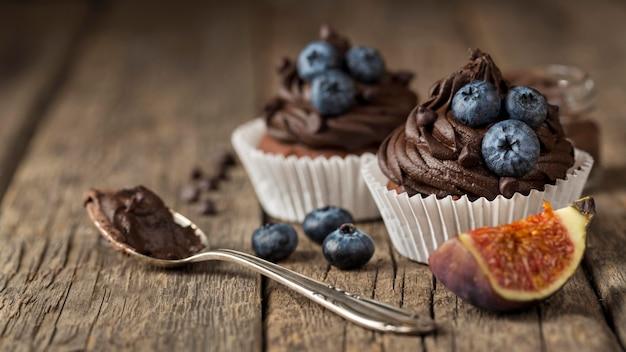 Высокий вид вкусный кекс и ложка с шоколадным кремом