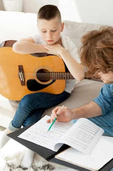 High view tutor and boy playing guitar