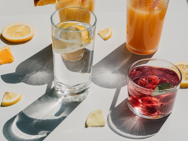 High view variety of containers with natural juice and water