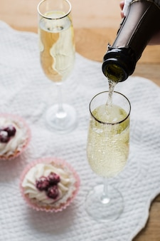 High view white wine glasses and bottle with cupcakes