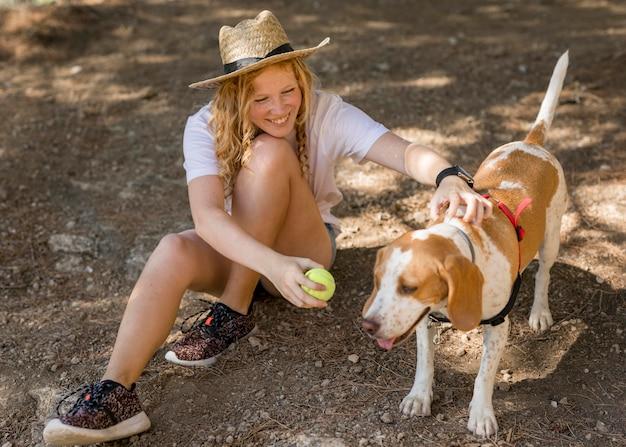 Женщина высокого вида и ее собака играет