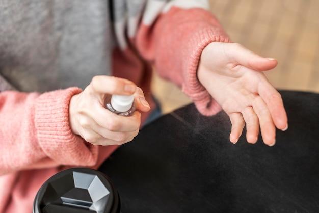 Высокий вид женщина, применяя дезинфицирующее средство на ее руках