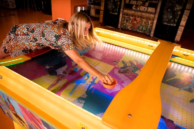 High view woman playing air hockey