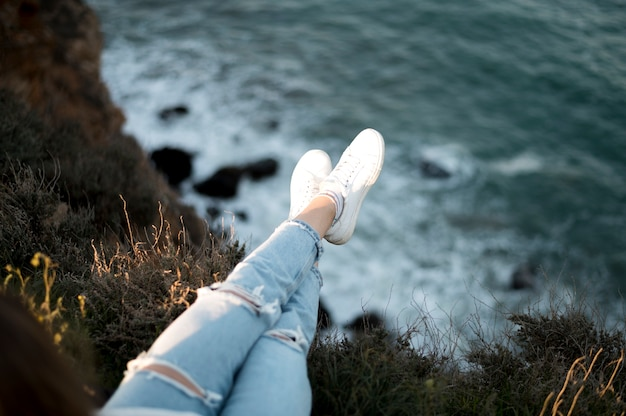 High view woman's legs and ocean